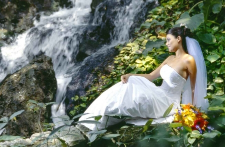 A bride sitting near a waterfall in the Riviera Mayan jungle.