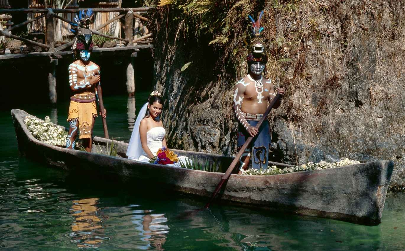 A bride being carried in a canoe by Mayan warriors.