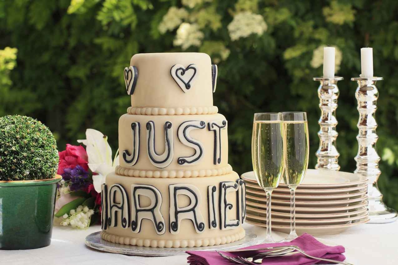 A wedding cake that says, JUST MARRIED, on it with champagne and serving utensils.
