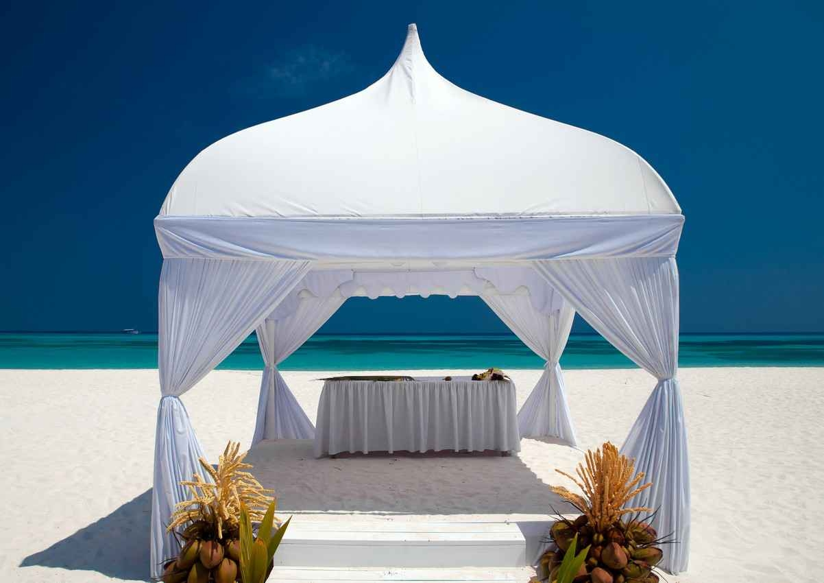 A wedding canopy on the Playa Del Carmen beach with calm water in the background.