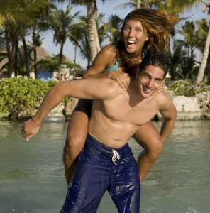 A man carrying a woman piggyback style on the water at Xcaret themepark.
