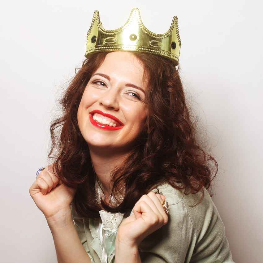 A crazy woman wearing a crown on her head and smiling ecstatically.