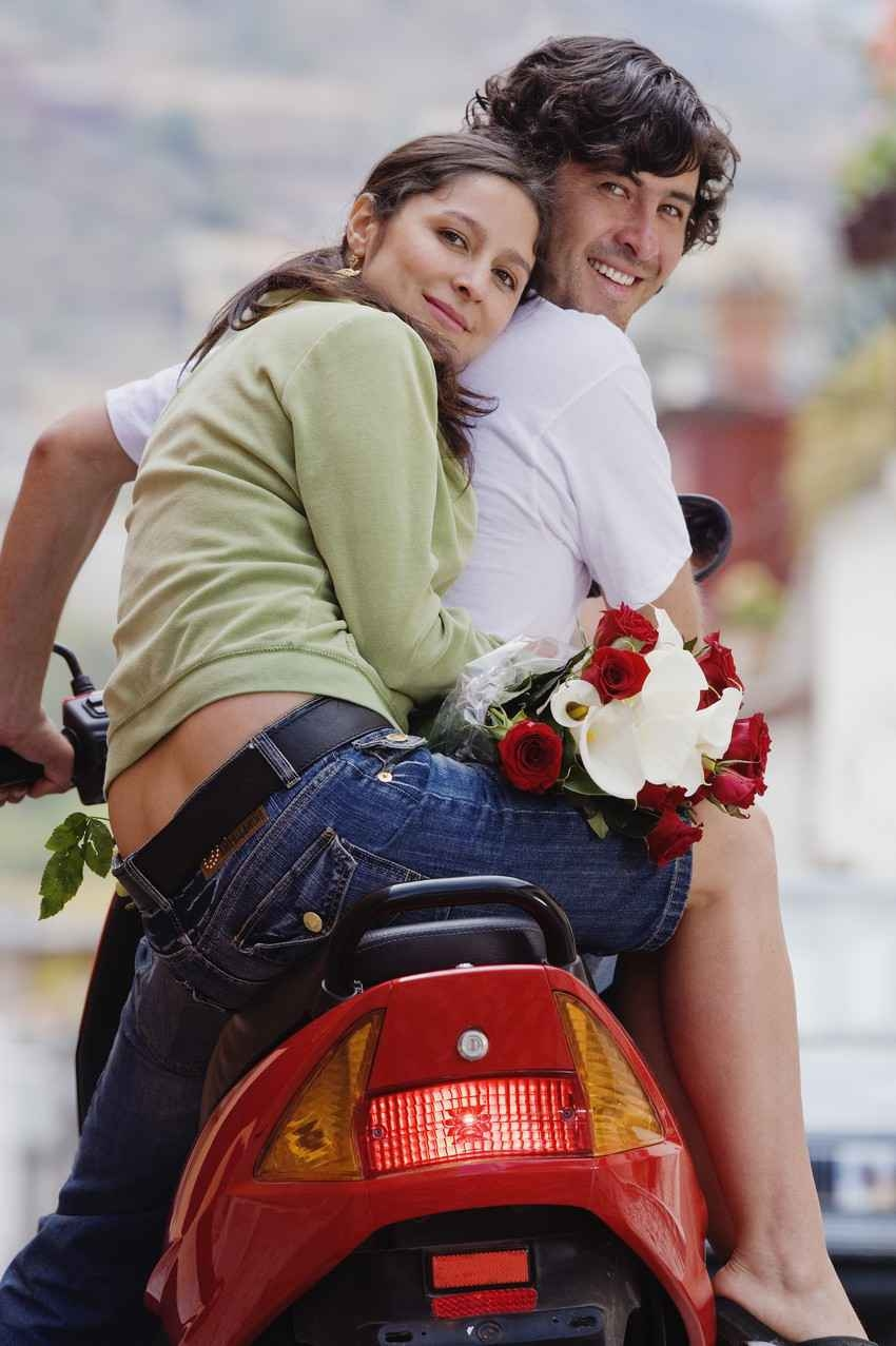 A couple on a honeymoon riding a scooter with the woman holding a bouquet of flowers.