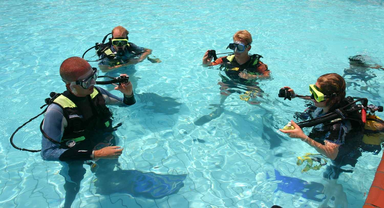 A scuba diving instructor working with three students in a swimming pool.