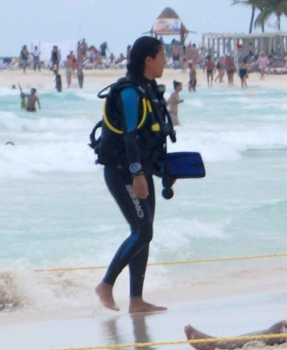 A woman on the beach in Playa Del Carmen who is wearing full scuba diving gear and walking out of the water.