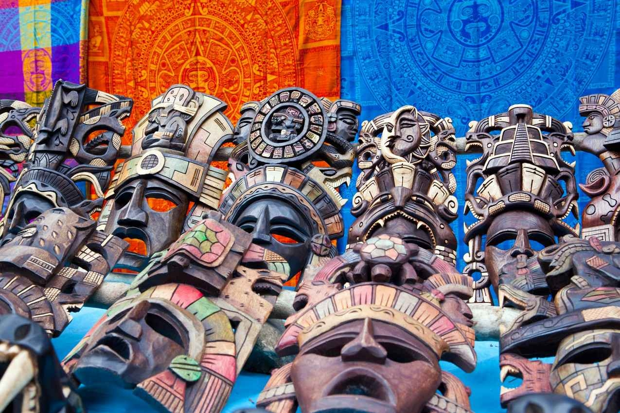 Several amazing and beautiful hand carved wooden Mayan masks for sale on the street.