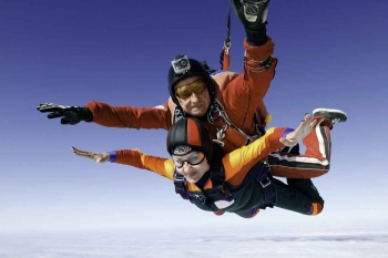 An older woman and a skydiving instructor doing a tandem jump together.