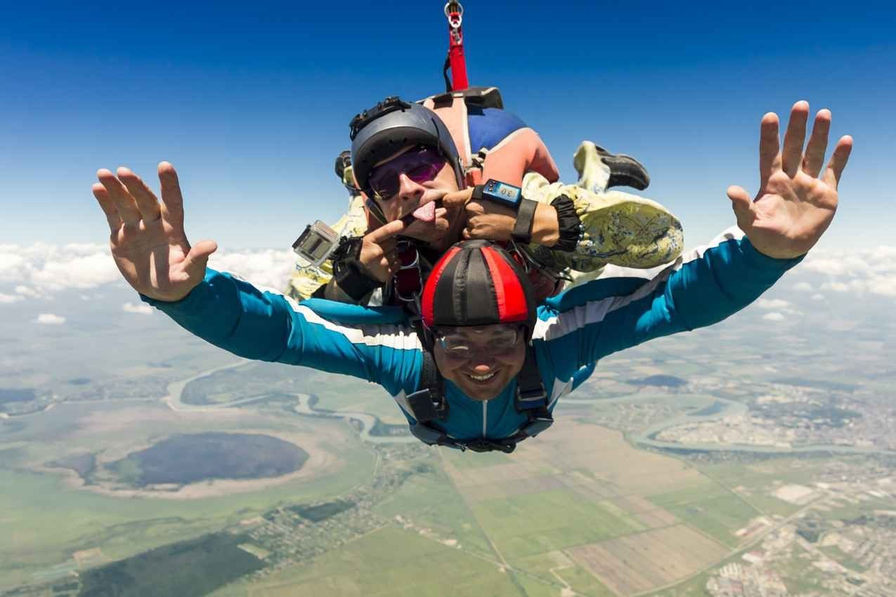 Several people skydiving over Playa Del Carmen while their instructor makes a funny face.