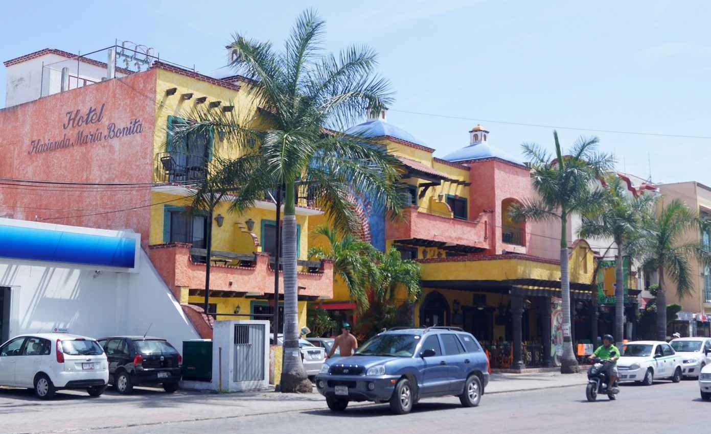 The front of a small hotel facing the street and traffic.