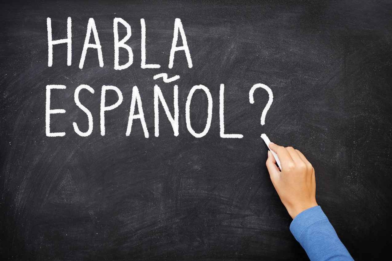 The Spanish words, habla espanol, written on a black chalkboard.