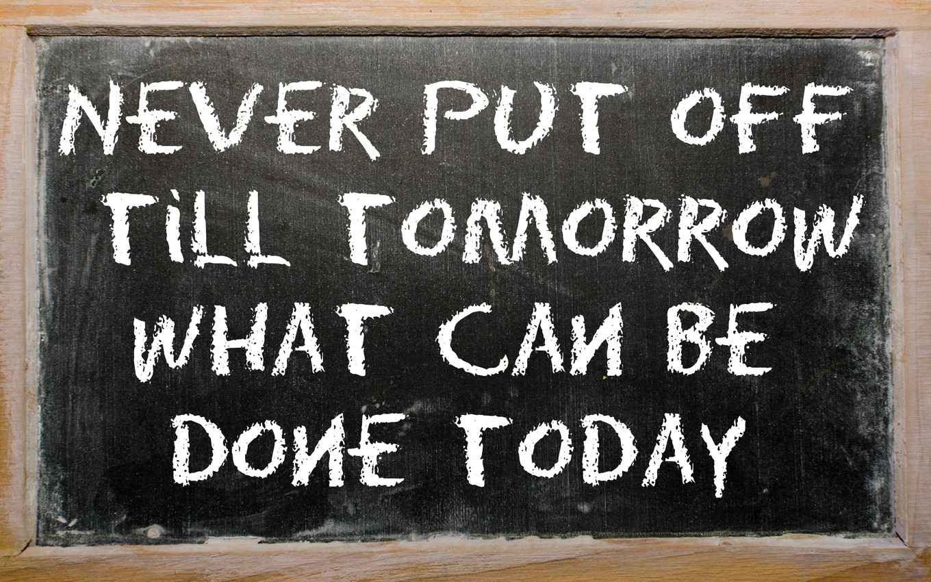 The words, never put off till tomorrow what can be done today, written on a chalkboard.