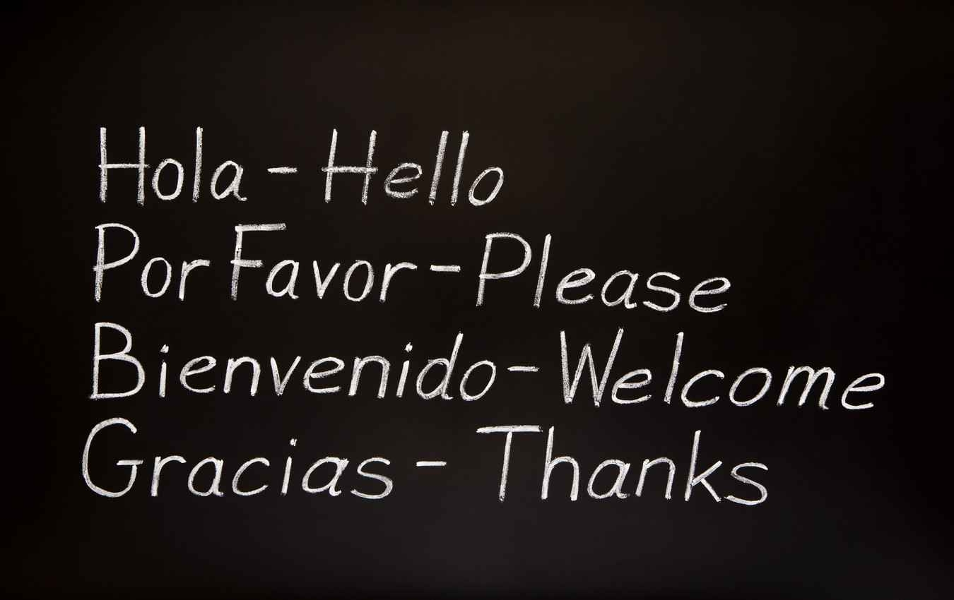 The words, hello, please, welcome, and thanks translated from Spanish to English and written on a black chalkboard.