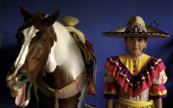 A Mexican horse rider standing near a horse with its mouth open.