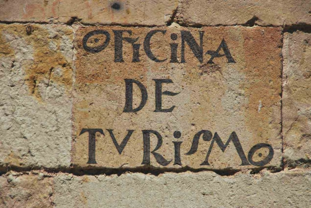 Stone wall with Oficina De Turismo written on it.
