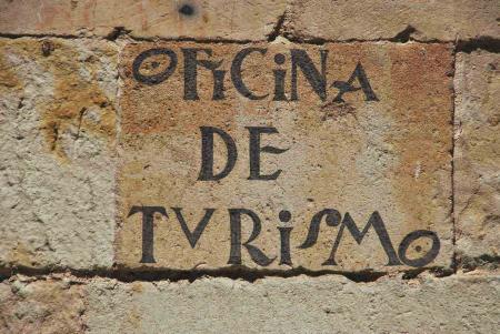 Stone wall with Oficina De Turismo written on it.