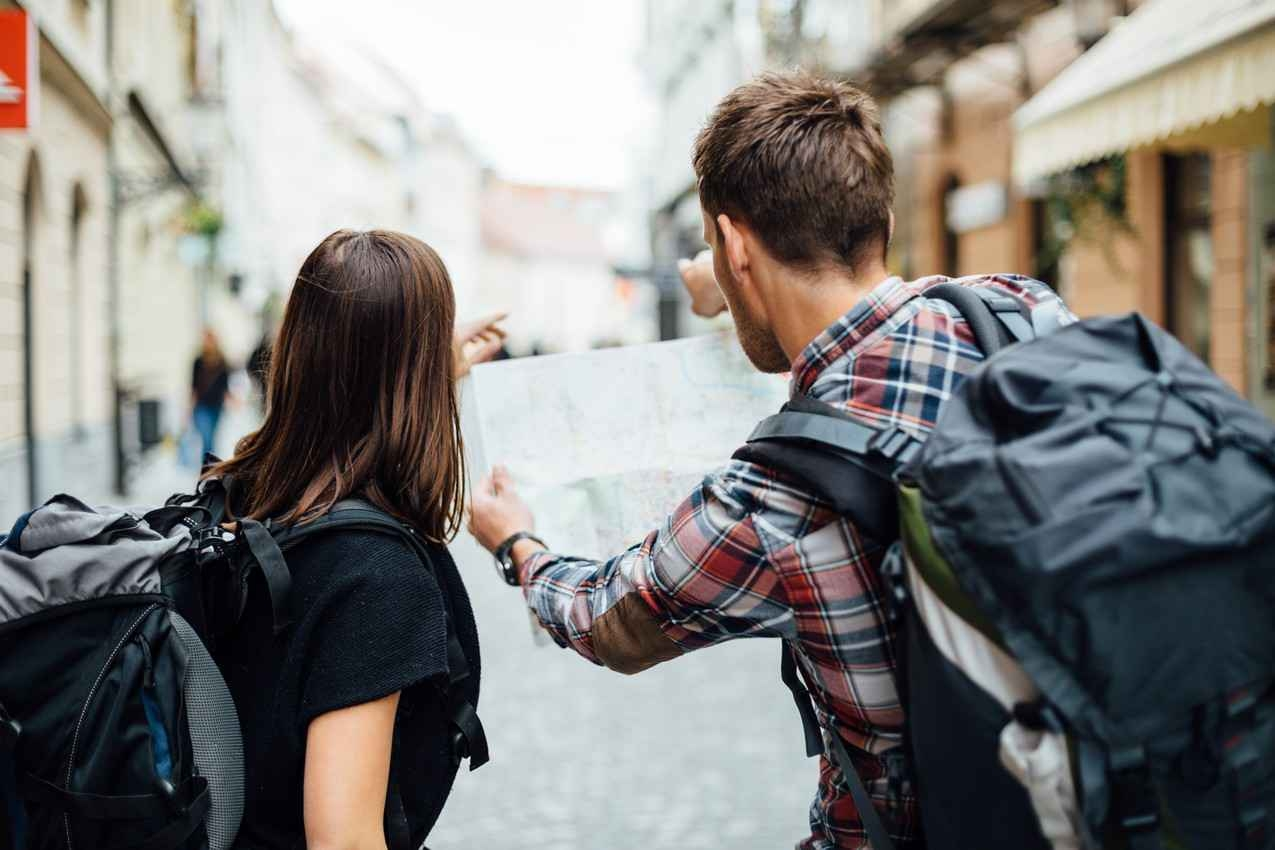 Several male and female student backpackers looking at a map for directions.