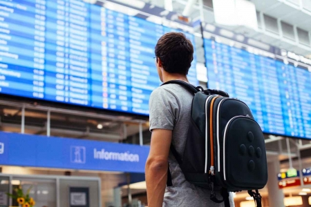 A male student with a backpack walking in an international airport.
