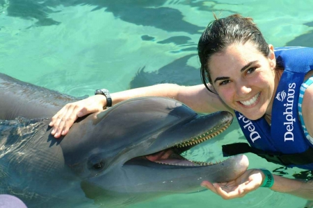 A girl swimming with a dolphin near Playa Del Carmen.