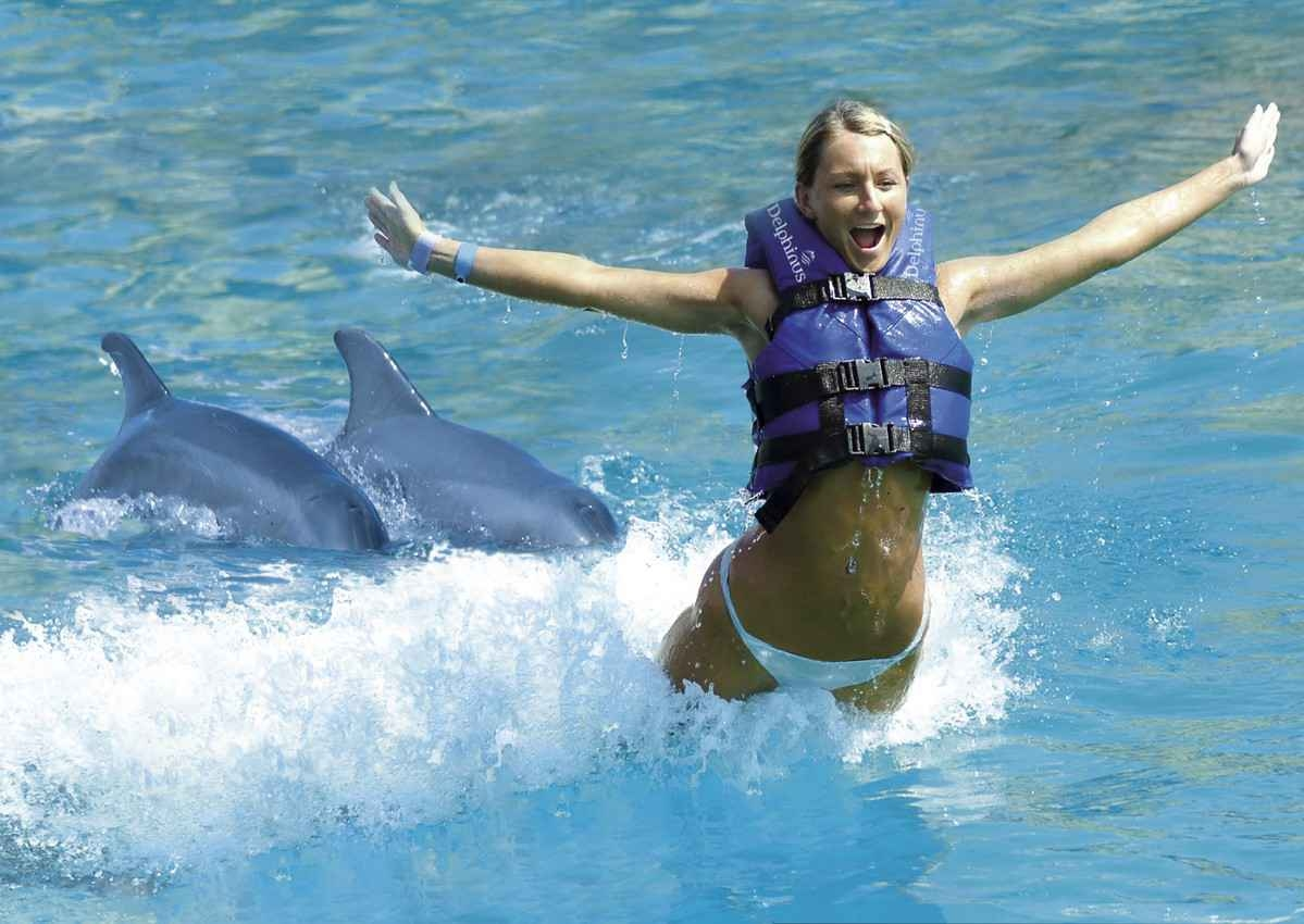A young woman is lifted in the air while she is being pushed by two dolphins.