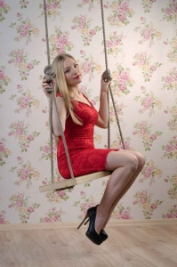 A cute blonde woman swinging on a wooden rope swing.