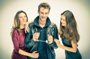 A cool guy wearing handcuffs with two beautiful women standing on each side of him.