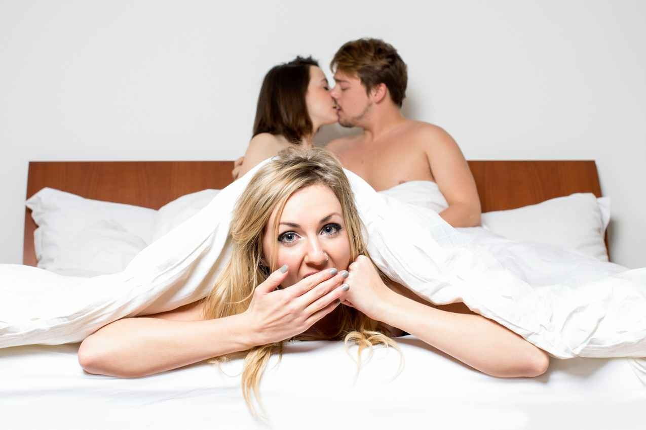 A woman and a another woman kissing a man under the blankets in a bed.