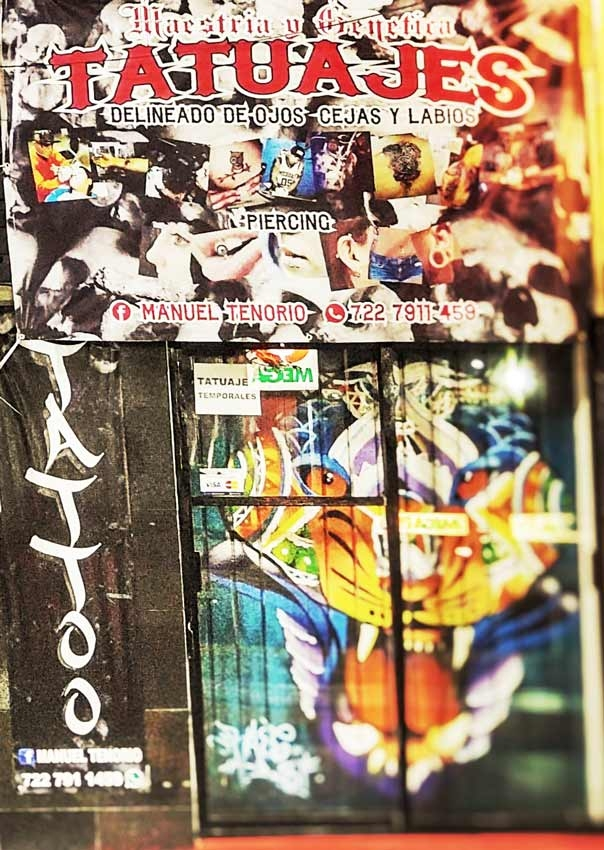 The door of a tattoo shop in Playa Del Carmen with lots of artwork on it.