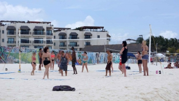 Several people playing beach volleyball in Playa Del Carmen.