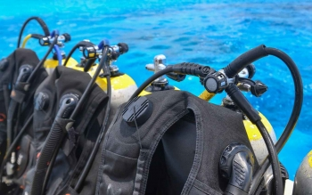 A long row of scuba diving tanks and equipment on a scuba diving boat.