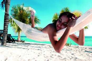 A woman is lying in a hammock with white sand and aqua blue water behind her.