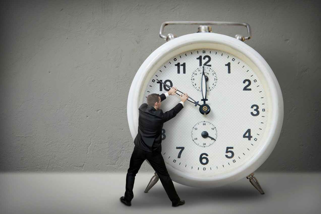 A man turning back the hands of a clock.