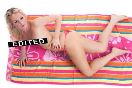 A woman without a bikini lying on a beach towel.