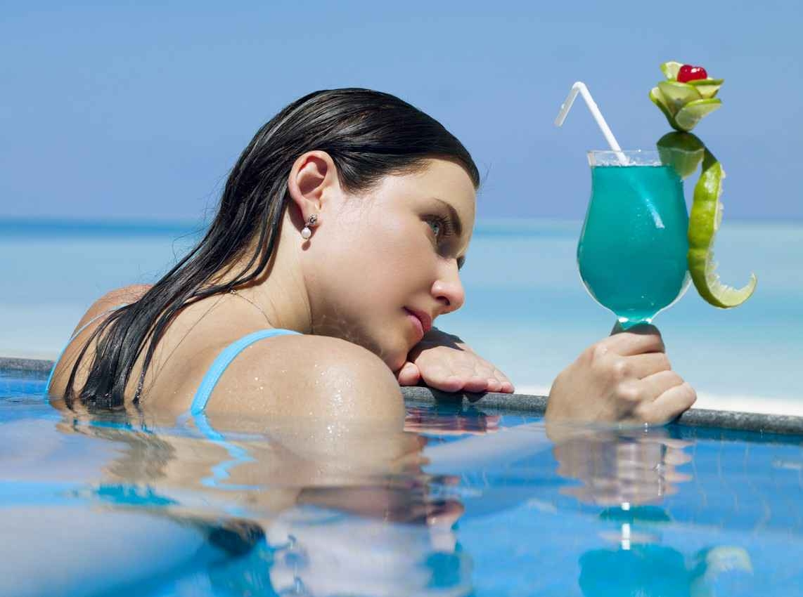 A beautiful woman in a swimming pool overlooking the beach holding a cocktail in her hand.