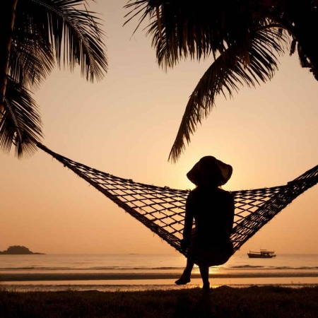 A woman sitting in a hammock with the beach in the background.