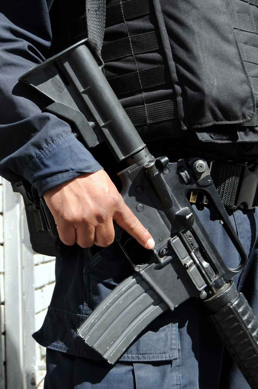 A Mexican police officer holding an automatic weapon.