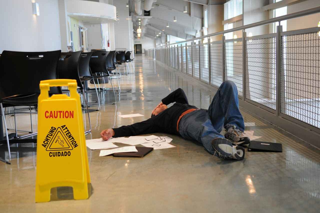 A man who slipped and fell dropping papers near a caution wet floor sign.