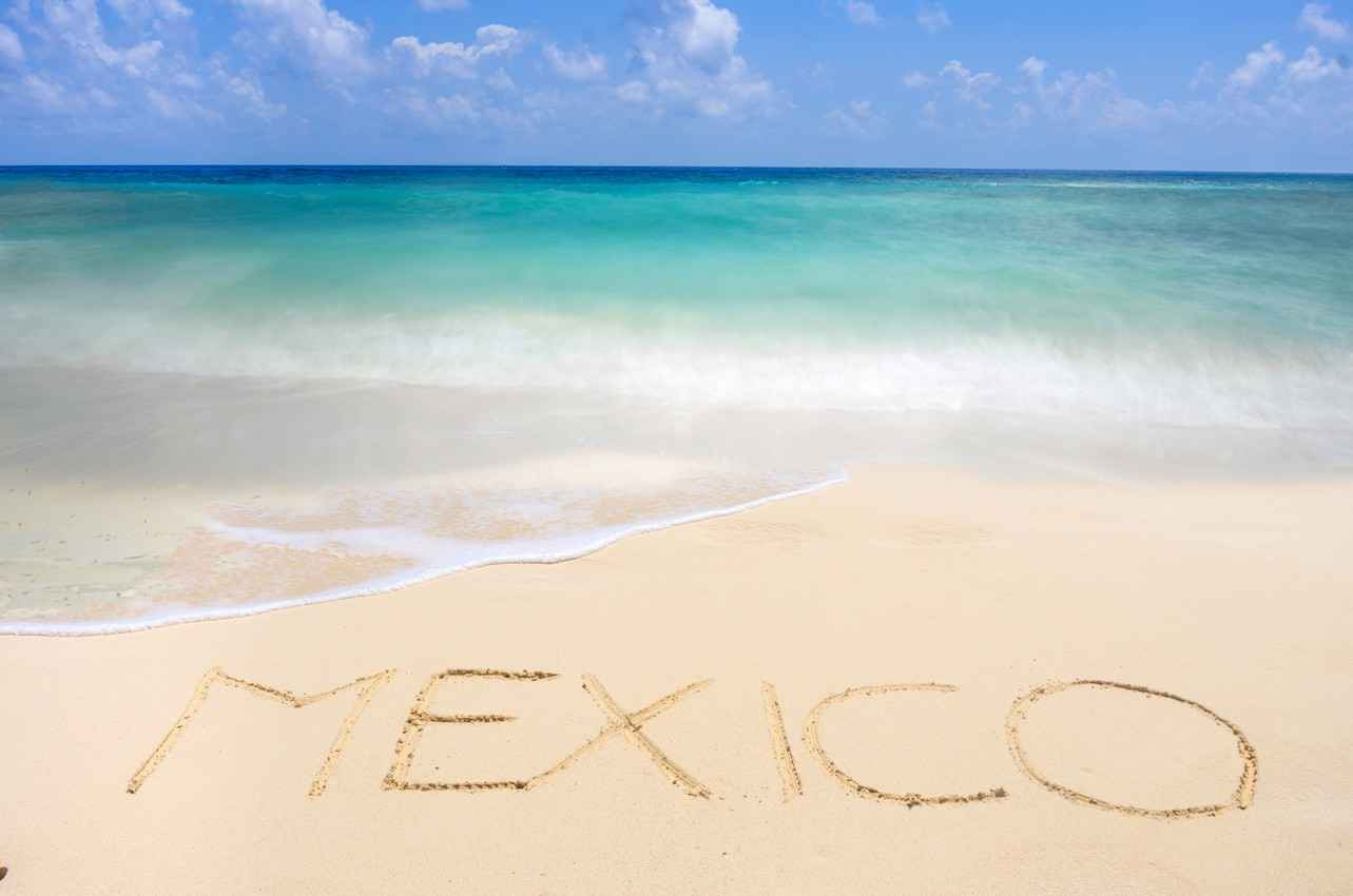 The word, Mexico, written in the sand and the Caribbean beach.