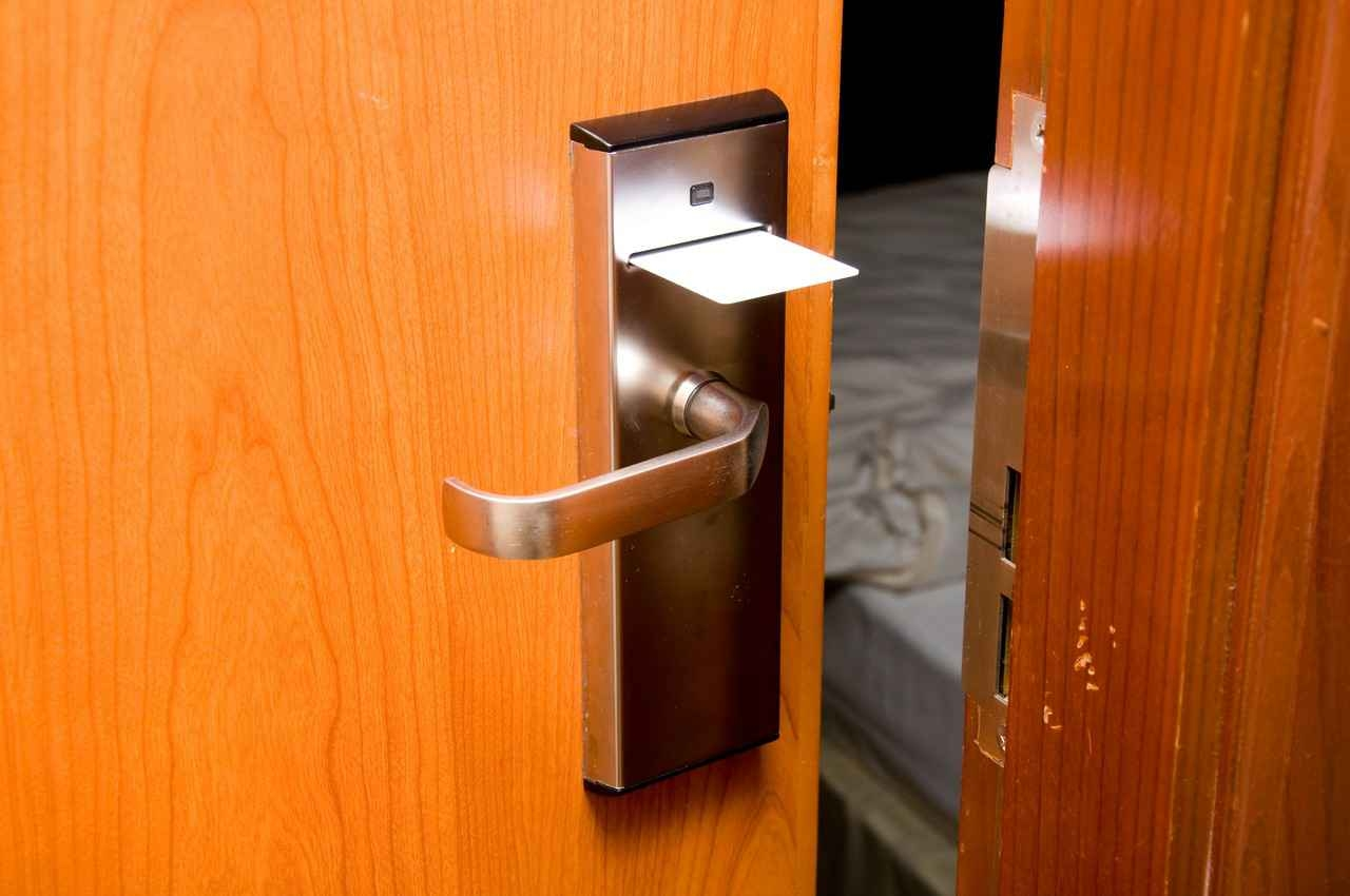 An open hotel room with the card entry key sticking out of the door.
