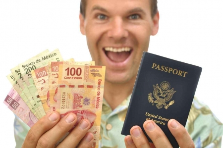 A man holding Mexican pesos and a US passport.
