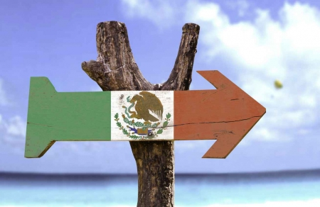 A Mexican flag arrow sign in front of the Caribbean Sea.
