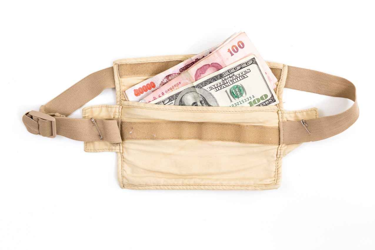 A money belt that is holding both dollars and Mexican pesos.
