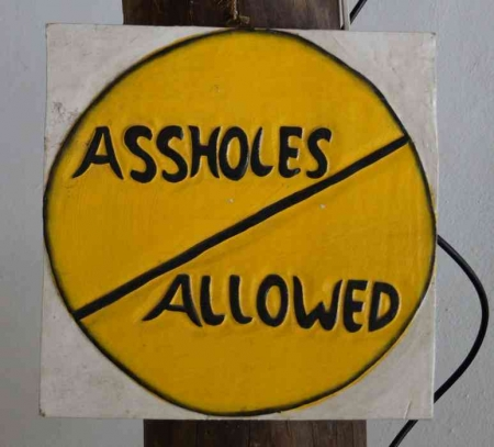 "A ""NO ASSHOLES ALLOWED"" sign."