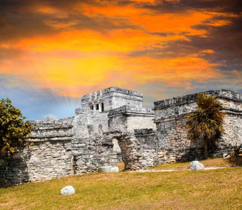 The Mayan ruins at Tulum with a beautiful sunset sky in the background.