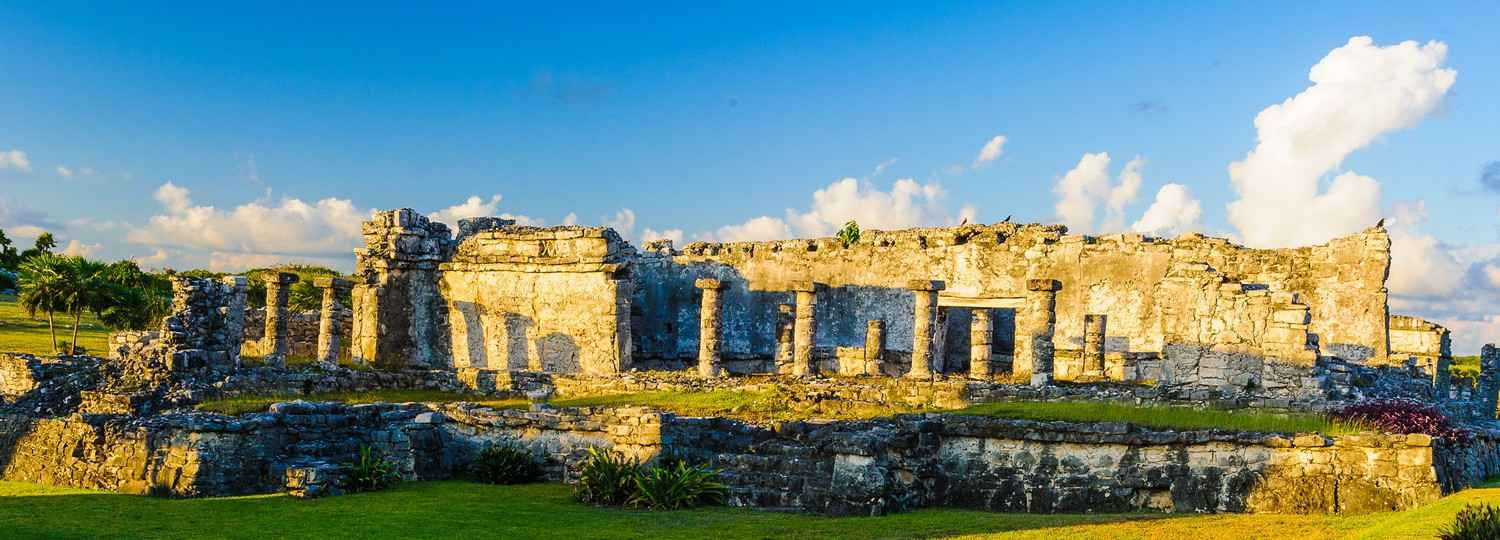 An extended portrait of the Mayan ruins at sunset.