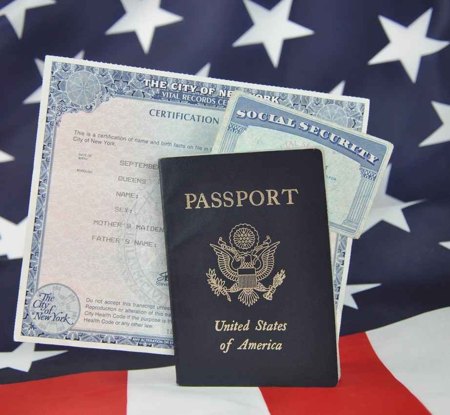 A passport, birth certificate, and Social Security card on top of an American flag.
