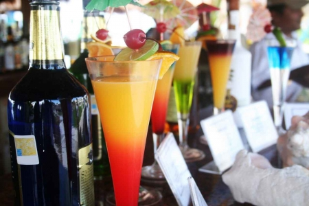 A number of various cocktails on a bar.