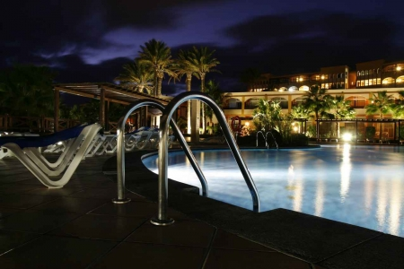 A resort swimming pool as seen at night.