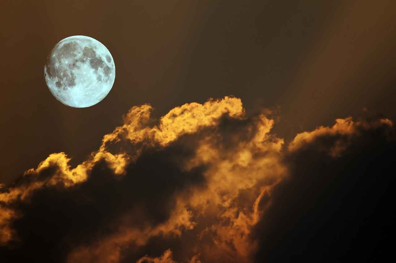 A bright and visible moon behind several clouds at night in Playa Del Carmen.