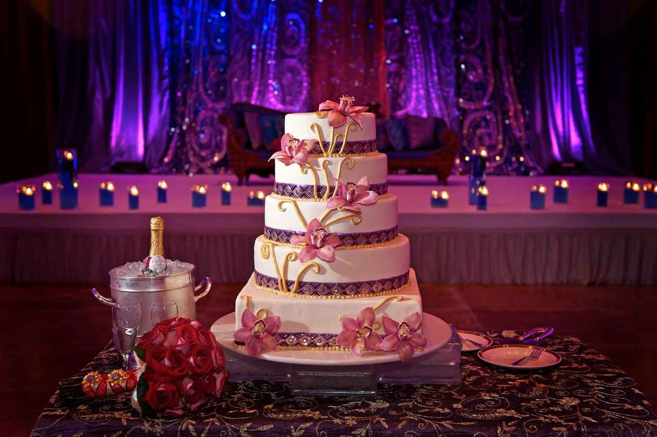 A wedding cake between several bottles of champagne and serving plates.