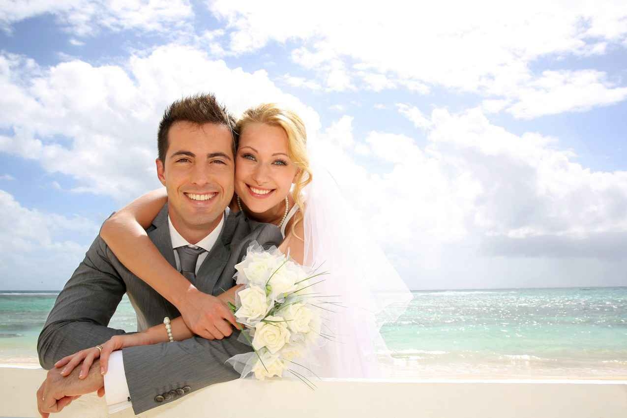A bride and groom on the beach with bright sun, white sand, and beautiful blue water visible behind them.